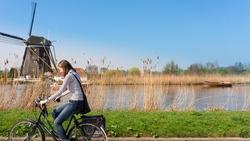 Woman bikes along windmill