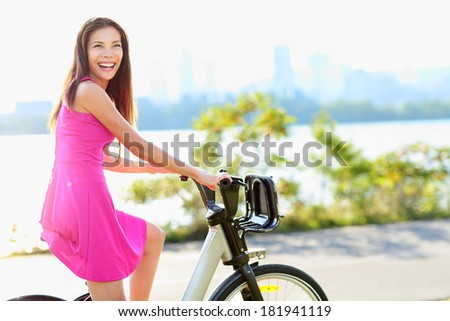 Woman biking in city park on bicycle. Happy girl on bike cycling outdoors in summer smiling of joy during outdoor activity.