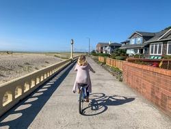 Woman biking on the Promenade in Seaside, Oregon