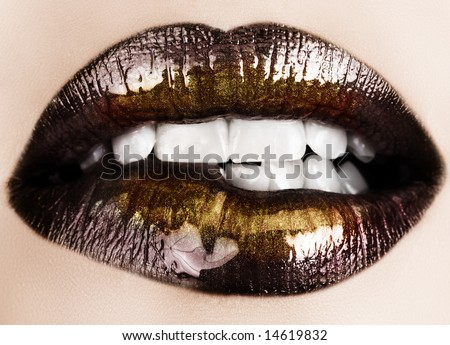 Woman biting her lips with black glossy lipstick and gold powder shine
