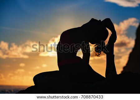 Woman black silhouette on sunset sky background. Young active girl sit in yoga pose on beach rock, stretching to keep fit. Healthy lifestyle, outdoor fitness, sports activity on summer family holiday. #708870433