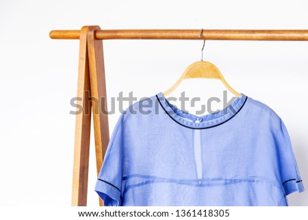 Woman blouse with blue blouse cotton on wooden hangers.