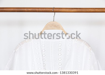 Woman blouse with White blouse linen on wooden hangers.
