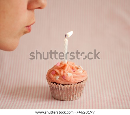 Woman blowing a candle on a pink cupcake - stock photo