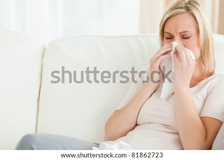 Woman blowing her nose in her living room
