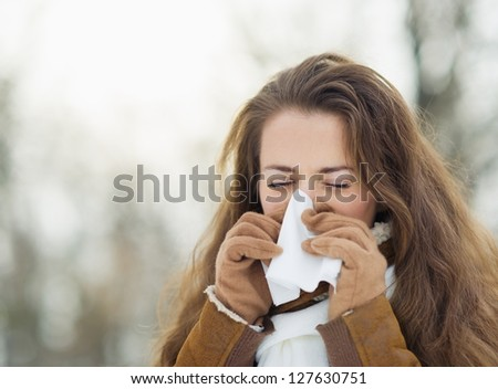 Woman blowing nose in winter outdoors