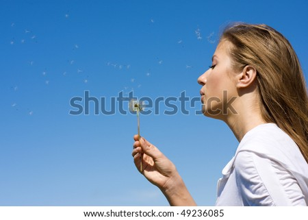 Woman blowing on white dandelion at blue sky