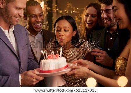 Woman Blowing Out Candles On Birthday Cake #623117813