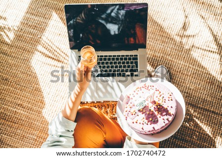 Woman blowing out the candle on the birthday cake and making video call. Girl celebrating birthday online in quarantine time. Close up birthday cake and laptop.