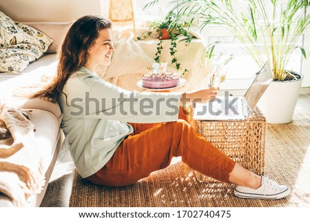 Woman blowing out the candle on the birthday cake and making video call. Girl celebrating birthday online in quarantine time.