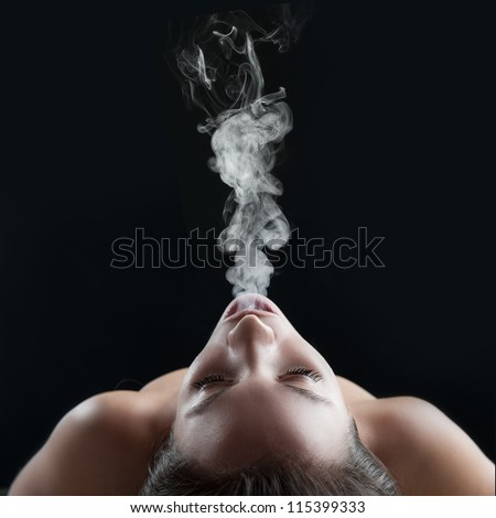 Woman blowing smoke against black background. Studio fashion photo.