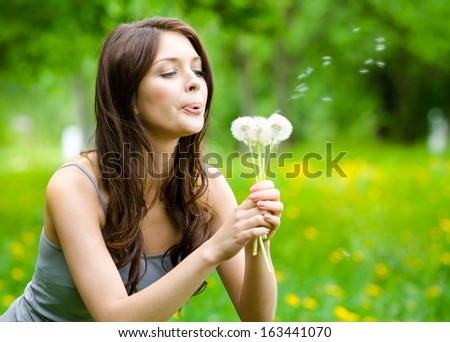 Woman Blows Dandelions In The Park. Concept Of Nature And Rest