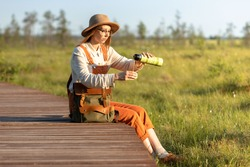 Woman botanist with backpack sitting on wooden path through peat bog swamp in wildlife national park. Naturalist resting on boardwalk, drinking tea, enjoying the moment at sunset. Ecotourism