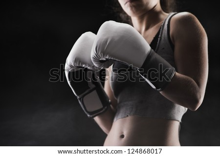 Woman boxer, focus on boxing glove, shallow deep of field