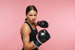Woman Boxer In Gloves Training On Pink Background
