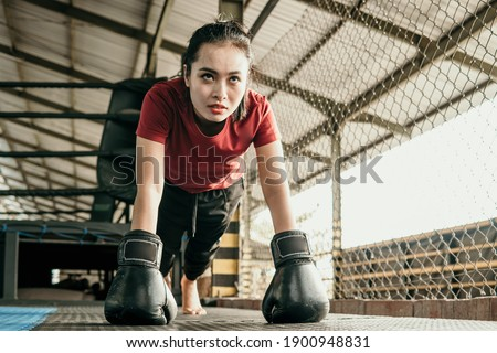woman boxer wearing black glove do push up when warming up before competing in the octagon Stock foto ©