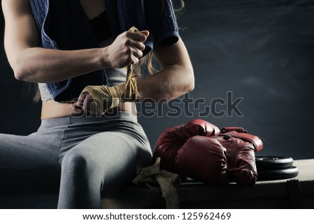 Woman boxer wearing white strap on wrist - stock photo