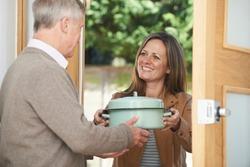Woman Bringing Meal For Elderly Neighbor