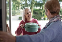 Woman Bringing Meal For Elderly Neighbour