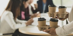 Woman brings take away paper cups of coffee come into office during group of employees, colleagues sitting and work at working desk and then they greeting and happy with kindness. Teamwork concept.