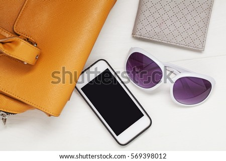 Woman brown leather bag with smartphone, glasses on white background. Top view.