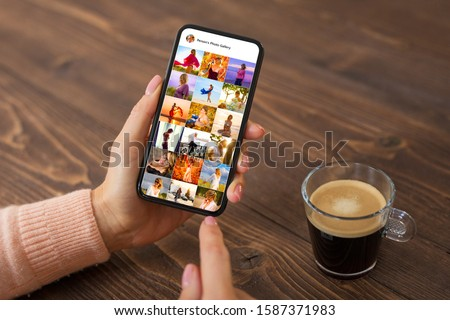 Woman browsing photos on social media app, person's name on screen is made up