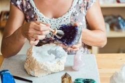 Woman brushing an amethyst in her workshop