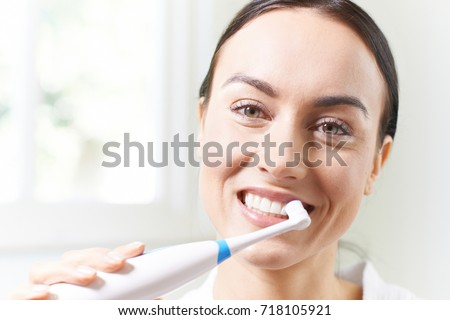 Woman Brushing Teeth With Electric Toothbrush In Bathroom #718105921