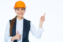 Woman builder in helmet points finger at copy space on white background. Thumb up. Smiling girl.