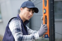 woman building metal fence checking regularly with a spirit level