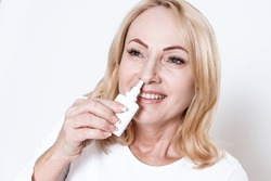 Woman buries her nose with a nasal spray and smiles. The blonde stands on a white background and bury her nose with the drug.