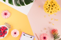 Woman business workplace with a laptop, flowers and green palm leaf on bright yellow and pink background. Top view of working space of a female at summer time. Flat lay