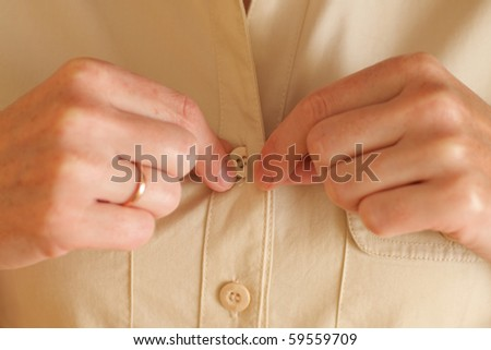 Woman buttoning her beige shirt