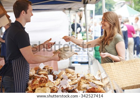 Woman Buying Bread From Market Stall - Shutterstock ID 342527414