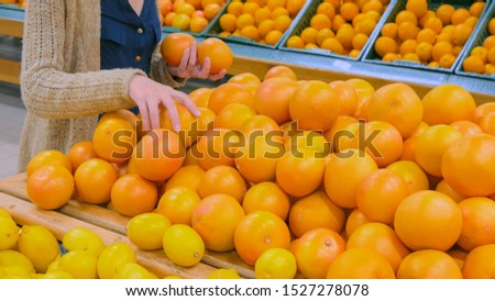 Woman buying fresh citrus fruits - grapefruits at supermarket. Consumerism, sale, organic and health care concept