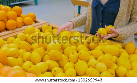 Woman buying fresh citrus fruits - yellow lemons at supermarket. Consumerism, sale, organic and health care concept