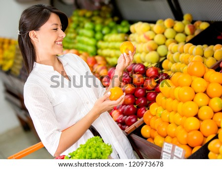 Woman buying fresh fruit at the supermarket