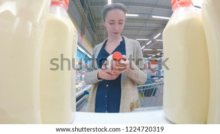 Woman buying fresh milk at grocery store. Point of view shot. Consumerism, sale, shopping and health care concept