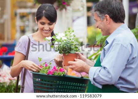 Woman buying plants in garden center - stock photo