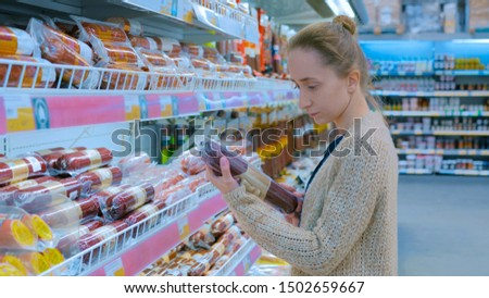 Woman buying sausage at grocery store. Consumerism, sale and shopping concept
