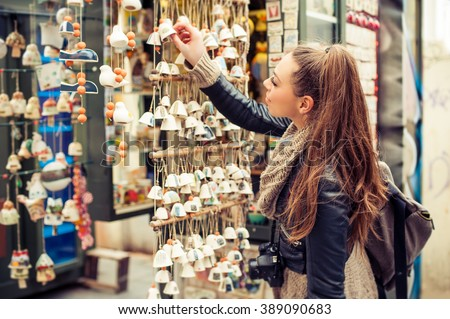 Shutterstock Woman buying souvenirs. Young woman buying souvenirs in gift shop