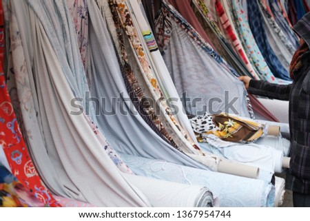woman buying textile, fabric rolls  and textiles on market