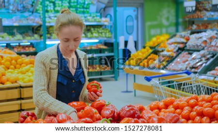 Woman buying vegetables - fresh red bell peppers at supermarket. Consumerism, sale, organic and health care concept