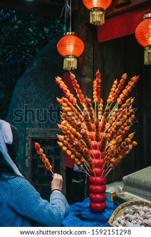Woman buys and holds traditional Chinese dessert Tanghulu also called bingtanghulu, is a snack of candied fruit. Hawthorn Gourd caramelized sour on bamboo skewer sold on tourist pedestrian street.