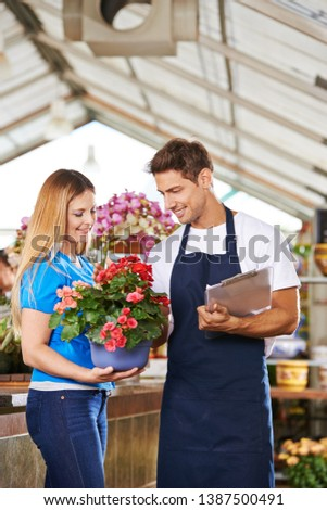 Woman buys Eliator begonias in the garden center at a florist #1387500491
