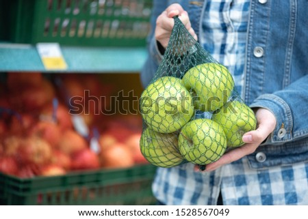 Woman buys fresh green apples at grocery store.