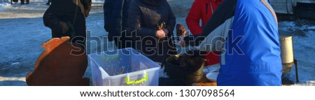 Woman buys grilled meat skewers in winter outside