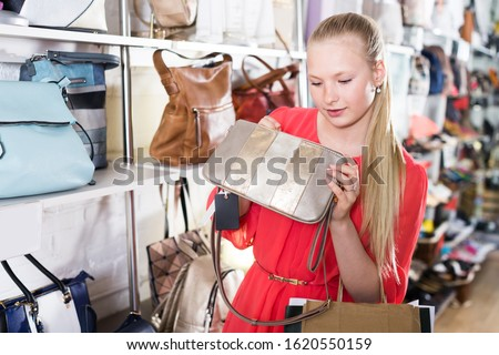 Woman buys new modern hand bag in boutique.