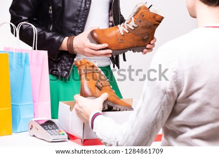 Woman buys shoes at the shop checkout.
