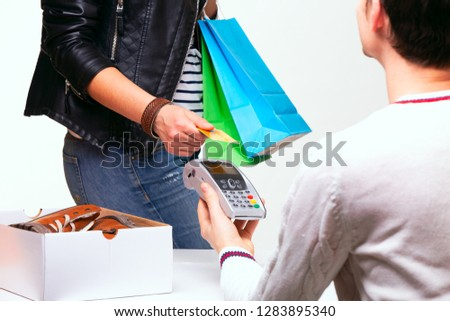 Woman buys shoes at the shop checkout, she is paying using a credit card.